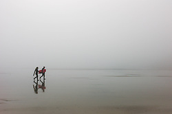© Licensed to London News Pictures. <br /> 08/05/2016. <br /> Saltburn by the Sea, UK.  <br /> <br /> Two body boarders walk from the water after a surf as heavy fog shrouds the coastline at Saltburn by the Sea in North Yorkshire as much of the country enjoys the hottest temperatures of the year so far.<br /> <br /> Photo credit: Ian Forsyth/LNP