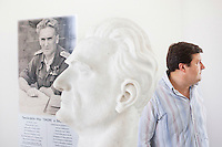 """AFFILE, ITALY - 23 AUGUST 2012: Mayor of Affile Ercole Viri, 52, stands by the bust of fascist Marshall Rodolfo Graziani in the mausoleum dedicated to him in Affile, a town with a population of 1,600 80km east of Rome, on August 23, 2012. A mausoleum and park, dedicated to the memory of Fascist Field Marshall Rodolfo Graziani, has recently been opened in the Italian town of Affile. At a cost of €127,000 to local taxpayers, the mayor Ercole Viri has expressed hope that the site will become as 'famous and as popular as Predappio' – the burial place of Mussolini which has become a shrine to neo-Fascists. Rodolfo Graziani was the youngest colonel in the Regio Esercito (Royal Italian Army), known as the """"Butcher of Fezzan"""" and the """"Butcher of Ethiopia"""" for the brutal military campaigns and gas attacks he led in Libya and Ethiopia under the dictatorship of Benito Mussolini under which he then became Minister of Defence from 1943 to 1945."""