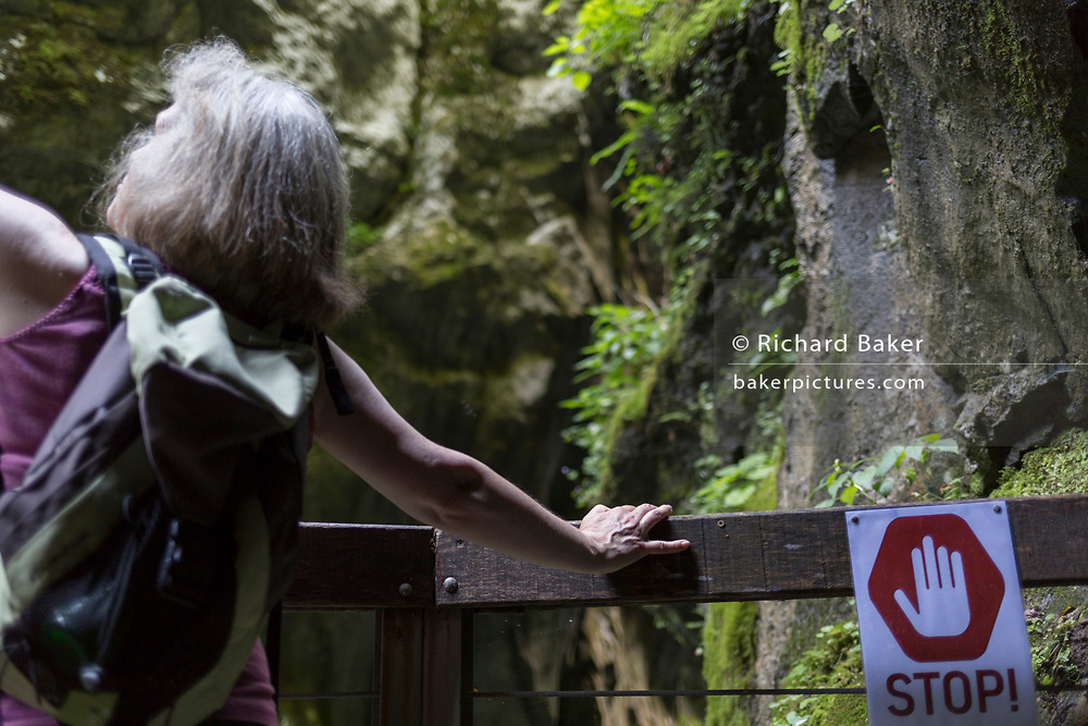A visitor and danger sign in Tolmin Gorge (Tolminska Korita), on 20th June 2018, in Tolmin Gorge , Slovenia.