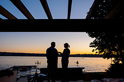 United States, Washington, Kirkland, couple on deck of home at sunset, by Lake Washington
