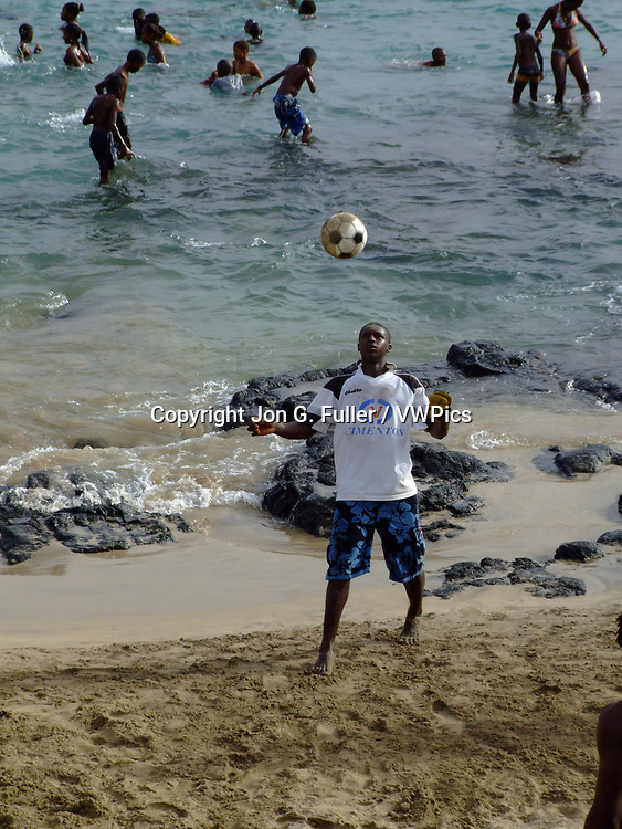 Young man bouncing a soccer ball off his head on the beach at Tarrafal, Santiago Island, Republic of Cabo Verde.