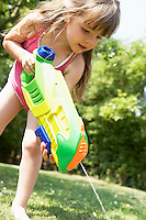 Little girl in park shooting water pistol into grass