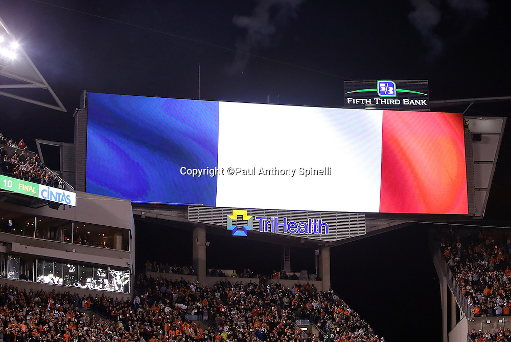 The stadium scoreboard is lit up red, white, and blue for the colors of the French flag during a moment of silence in tribute to those who lost their lives and were injured in the French terrorist attack in Paris before the Cincinnati Bengals 2015 week 10 regular season NFL football game against the Houston Texans on Monday, Nov. 16, 2015 in Cincinnati. The Texans won the game 10-6. (©Paul Anthony Spinelli)