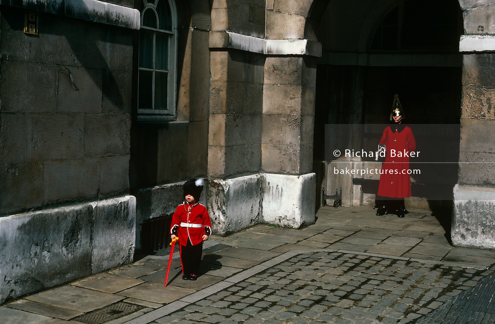 While visiting London's tourist sites, a young boy of about 5 years-old spends time at Horse Guards where a soldier from the Household Cavalry, also dressed in a deep red coat, stands motionless and at-ease. It is a bright day and the gray stonework amplifies the scarlett uniform tunics as the boy has his picture taken by family. The British Household Cavalry is classed as a corps in its own right, and consists of two regiments: Life Guards (British Army) and the Blues and Royals (Royal Horse Guards and 1st Dragoons). They are the senior regular regiments in the British Army, with traditions dating from 1660.