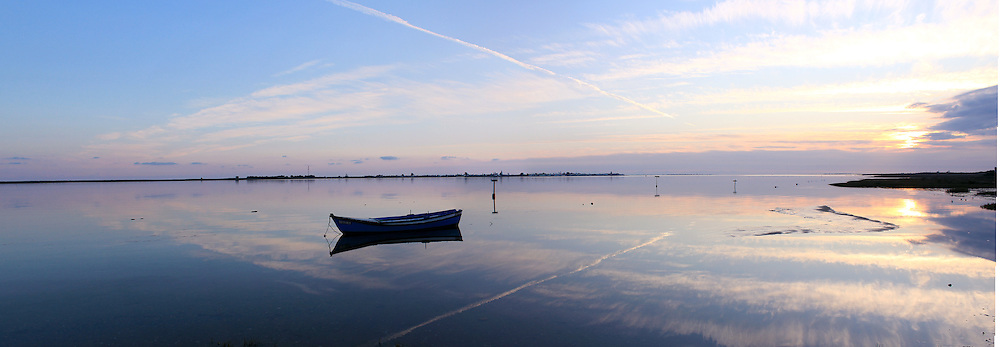 Traditional boat at sunset, in Ria Formosa, natural conservation region in Algarve, Portugal.