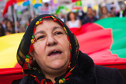 London, October 19th 2014. Hundreds of London's Kurdish community march throgh the capital in protest against ISIS and the Turkish government who they accuse, by not getting involved in military action against ISIS, of using the Jihadists to wipe out Kurds who have long been campaigning for an independent Kurdistan. PICTURED: A woman in traditional Kurdish dress chants slogans as she marches on Regents Street.