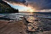Rocky Beach at sunset and incoming rain storm, on Kauai, Hawaii Island, USA.