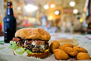 A Phil-Up burger, featuring bacon and slivered country ham, fried corn nuggets, and a bottle of IBC rootbeer, sits on a table at Phillip's Grocery Sept. 19, 2011 in Holly Springs, Miss. The saloon-turned-burger joint has become a mecca for tourists and travel writers. In 1989, USA Today named the burger among the top three in the nation. (Photo buy Carmen K. Sisson/Dispatch Staff)