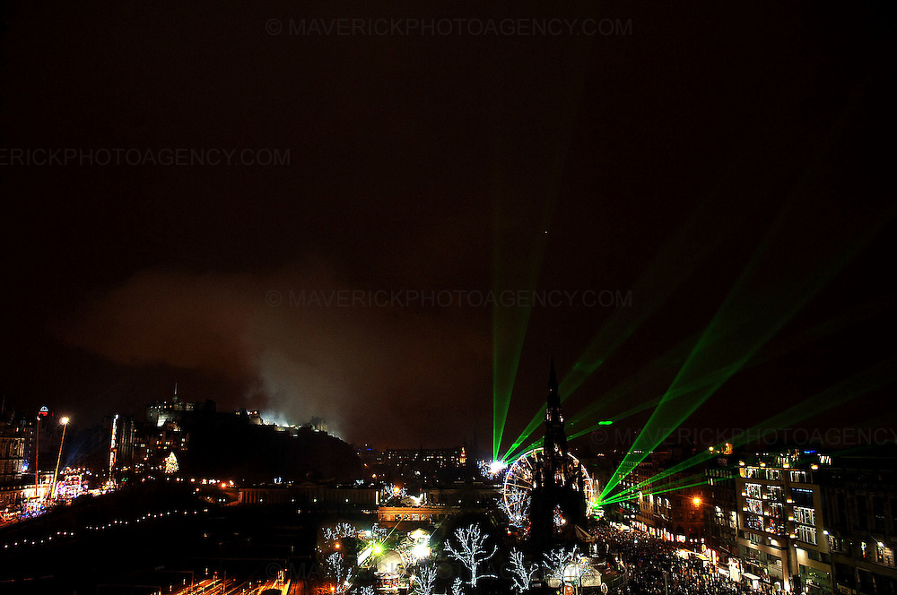 EDINBURGH, UK. Early revellers hit Princes Street in Edinburgh leading up to the bells at midnight...Pic shows the laser display after the fireworks...Picture Richard Scott/Maverick