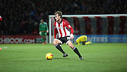 Brentford midfielder John Swift setting up an attack with an injnured boro player in the background during the Sky Bet Championship match between Brentford and Middlesbrough at Griffin Park, London, England on 12 January 2016. Photo by Matthew Redman.
