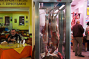 Easter lunch, Xania Market, Crete, Greece. Man eats his Good Friday lunch beside a butcher shop selling sheep carcasses for consumption on Easter Sunday, part of a Greek orthodox tradition.<br /> <br /> Editorial use only.