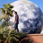 Man standing on brick wall in front of LPG tank painted as planet earth.