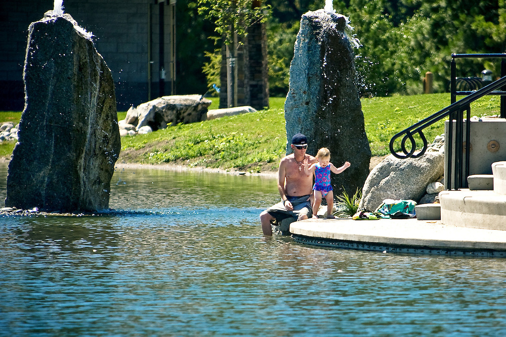 Michael Stocklen and his daughter Shayla cool off on the water's edge Monday at Riverstone Park. Swimming is not permitted in the newly opened pond, but most visitors find the park's layout inviting toward swimming with stairs that lead directly  to the water.