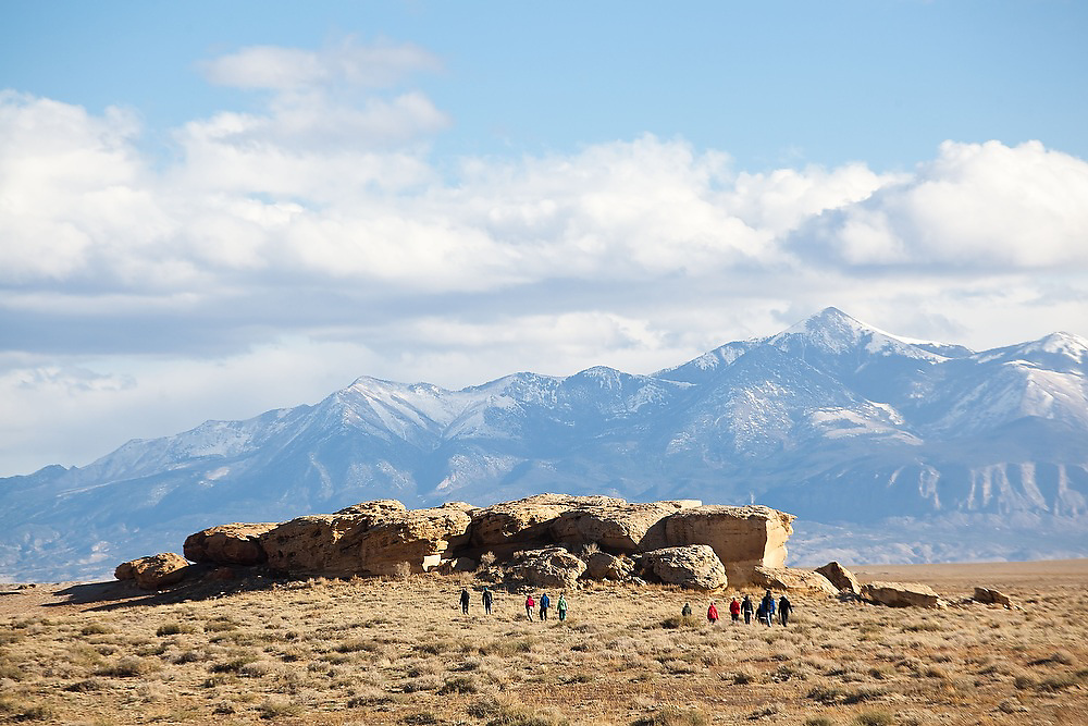 A group of students from the University of Colorado hike towards their camp on BLM land near Hanksville, Utah. The Henry Mountains are visible in the background.