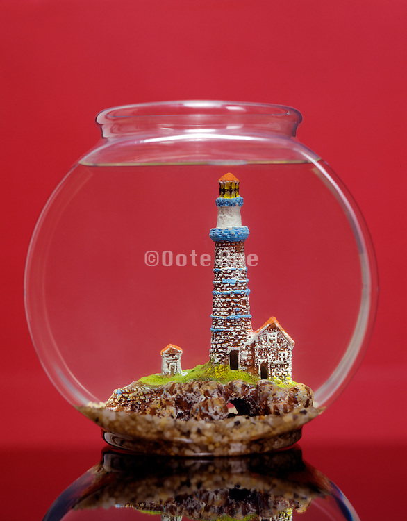 fish bowl with lighthouse against red background