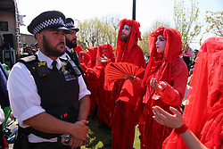 © Licensed to London News Pictures. 20/04/2019. London, UK. A large police prescience stood next to protestors at Waterloo bridge on the sixth day of protests by Extinction Rebellion. Protesters are demanding urgent government action on climate change. Photo credit: Sean Hawkey/LNP