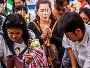 29 DECEMBER 2013 - BANGKOK, THAILAND:  People pray and light incense for the Patriarch at Wat Bowon Niwet in Bangkok. Somdet Phra Nyanasamvara, who headed Thailand's order of Buddhist monks for more than two decades and was known as the Supreme Patriarch, died Oct. 24 at a hospital in Bangkok. He was 100. He was ordained as a Buddhist monk in 1933 and rose through the monastic ranks to become the Supreme Patriarch in 1989. He was the spiritual advisor to Bhumibol Adulyadej, the King of Thailand when the King served as monk in 1956. There is a 100 day mourning period for the Patriarch. Although the Patriarch was a Theravada Buddhist, he was the Supreme Patriarch of all Buddhists in Thailand, including the Mahayana sect, which is based on Chinese Buddhism.       PHOTO BY JACK KURTZ