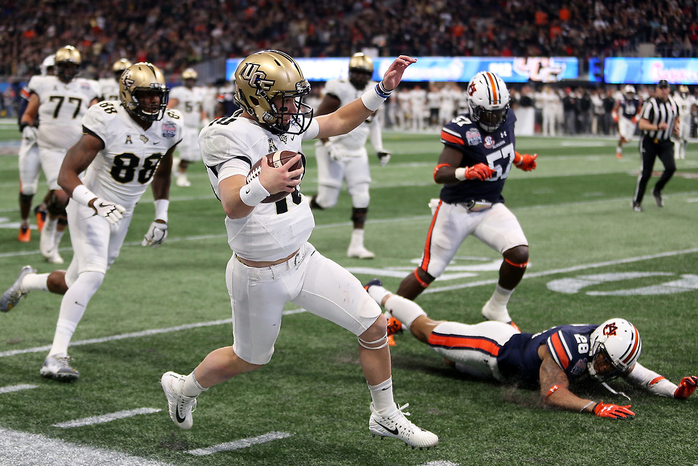 UCF Knights quarterback McKenzie Milton (10) runs the ball during the 2018 Chick-fil-A Peach Bowl NCAA football game against the Auburn Tigers on Monday, January 1, 2018 in Atlanta. (Jason Parkhurst / Abell Images for the Chick-fil-A Peach Bowl)