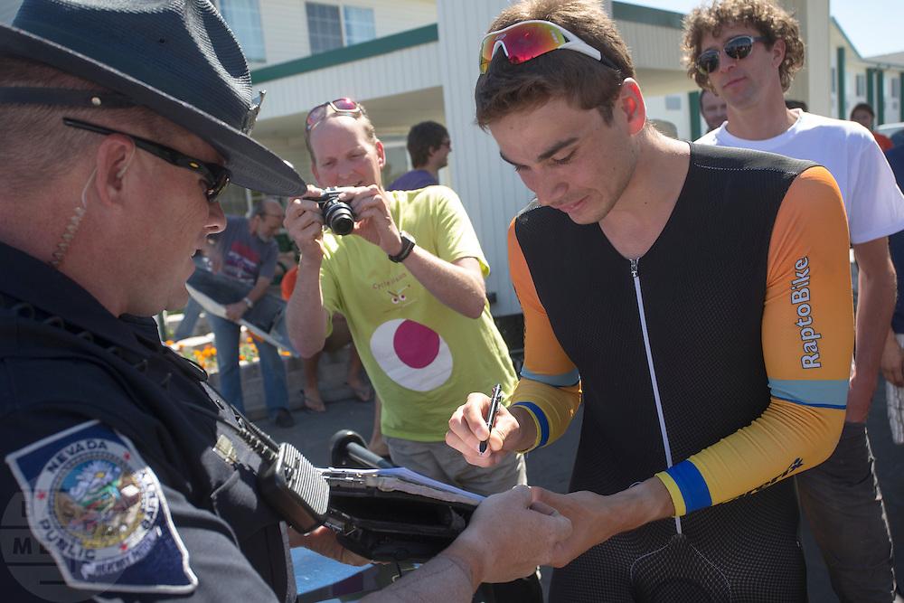 Een politieagent geeft de fietsers die boven de 70 mph hebben gereden een bon. De zesde racedag van de WHPSC. In de buurt van Battle Mountain, Nevada, strijden van 10 tot en met 15 september 2012 verschillende teams om het wereldrecord fietsen tijdens de World Human Powered Speed Challenge. Het huidige record is 133 km/h.<br /> <br /> A police officer gives all riders who pedaled above 70 mph a speeding ticket. The sixth day of the WHPSC. Near Battle Mountain, Nevada, several teams are trying to set a new world record cycling at the World Human Powered Vehicle Speed Challenge from Sept. 10th till Sept. 15th. The current record is 133 km/h.