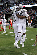 Oakland Raiders wide receiver Amari Cooper (89) leaps and celebrates with Oakland Raiders tight end Clive Walford (88) after Cooper catches a 45 yard first quarter touchdown pass good for a 14-10 first quarter lead during the 2017 NFL week 7 regular season football game against the against the Kansas City Chiefs, Thursday, Oct. 19, 2017 in Oakland, Calif. The Raiders won the game 31-30. (©Paul Anthony Spinelli)