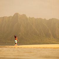 female walking exposed sand bar in Kaneohe Bay, Koolau Mountains at Kualoa as backdrop