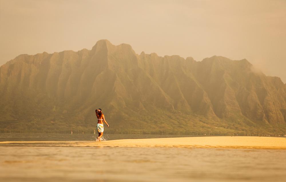 female walking exposed sand bar in Kaneohe Bay, Koolau Mountains at Kualoa as backdrop