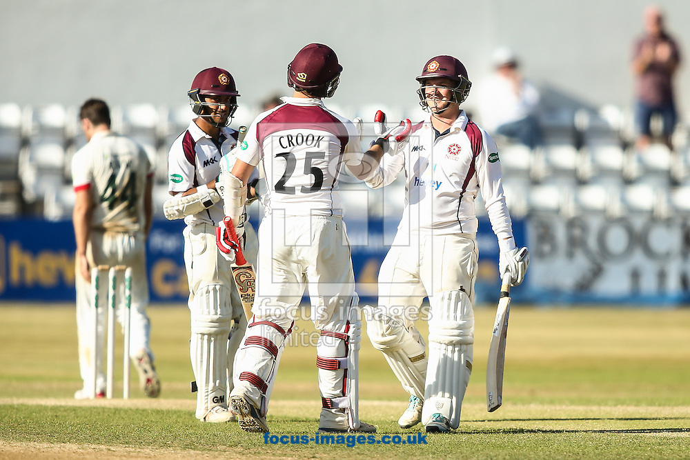 Rob Newton of Northamptonshire CCC (right) celebrates with his teammates after reaching his double-century during the Specsavers County C'ship Div Two match at the County Ground, Northampton<br /> Picture by Andy Kearns/Focus Images Ltd 0781 864 4264<br /> 15/08/2016