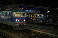 A man steps into the locomotive of a train soon to depart the station in the Crimean capital of Simferopol, in Ukraine. Passengers are walking outside a train on another platform