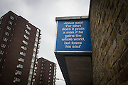 'Jesus said' Biblical quotations on a city church and bleak background tower blocks in the London borough of Southwark. Locals in these bleak south London streets may be uplifted by the words from the Christian scriptures, comforting the troubled with messages of humanity from the Bible, perhaps guiding Londoners incarcerated in the depressing 1960s tower block high-rises, homes to the poor and the dispossessed.