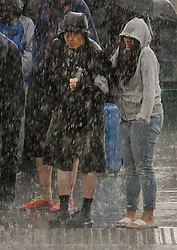 © Licensed to London News Pictures. 18/08/2017. London, UK. Tourists near Parliament get a soaking as a sudden burst of heavy rain hits central London. Today's weather has been a mixture of sunshine and showers for most of the UK. Photo credit: Peter Macdiarmid/LNP