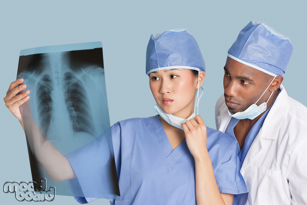 Two surgeons examining x-ray report over light blue background