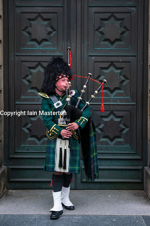 Scottish piper playing bagpipes on Royal Mile outside Edinburgh High Court in Edinburgh Old Town, Scotland ,UK