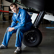 Connor Dimmock, an apprentice engineer sits on the wheels of a MK1 Spitfire