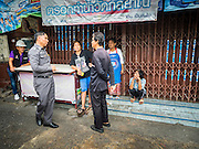 10 SEPTEMBER 2015 - BANGKOK, THAILAND:  Thai police talk to people in front of Chaiyasit Kittiwanitchapant's home at Wat Kalayanamit. Authorities started to destroy 54 homes in front of Wat Kalayanamit, a historic Buddhist temple on the Chao Phraya River in the Thonburi section of Bangkok. Government officials, protected by police, seized the house of Chaiyasit Kittiwanitchapant, a Kanlayanamit community leader, who has led protests against the temple's abbot for trying to evict community members whose houses are located around the temple. Work crews went into Chaiyasit's home and took it apart piece by piece. The abbot of the temple said he was evicting the residents, who have lived on the temple grounds for generations, because their homes are unsafe and because he wants to improve the temple grounds. The evictions are a part of a Bangkok trend, especially along the Chao Phraya River and BTS light rail lines, of low income people being evicted from their long time homes to make way for urban renewal.    PHOTO BY JACK KURTZ