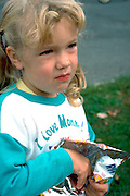 Girl eating potato chips at Catholic School bike-a-thon age 3.  St Paul Minnesota USA