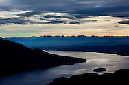 A cloud bank obscures the sunrise above lake TeAnau as seen from the Kepler Trak in Fiordland National Park in New Zealand's South Island.