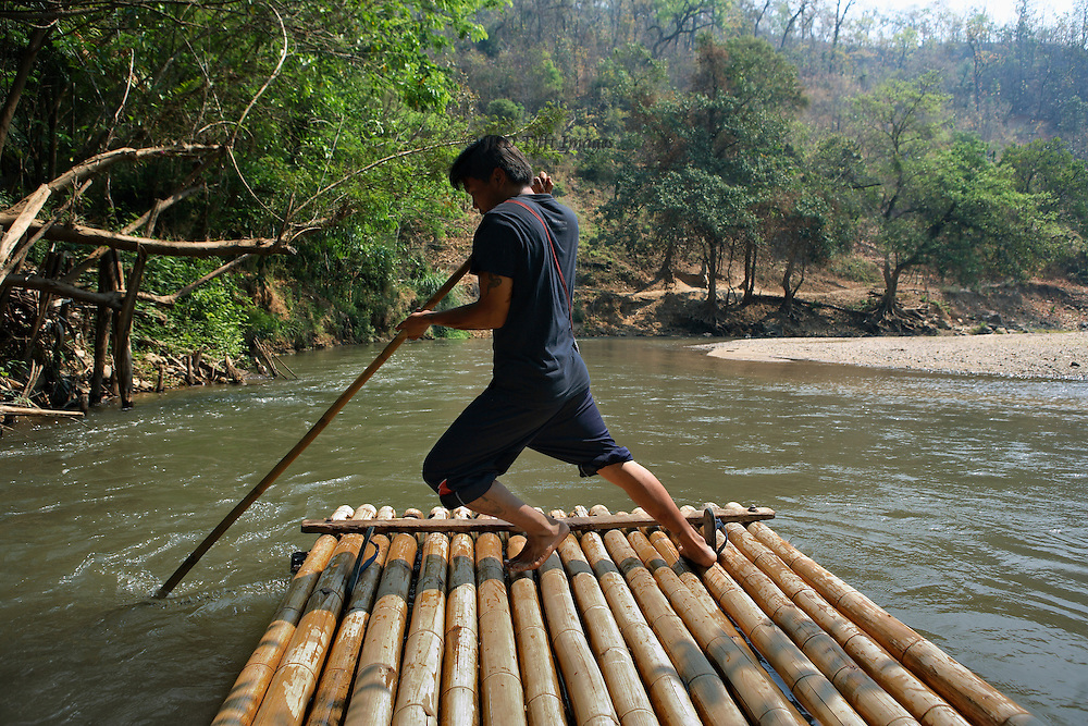 Passenger's viewpoint on a raft of thin logs lashed together.  The rafter pushes hard with his pole to keep the little vessel away from the river bank.  Forest, sandbar, and smooth river water.