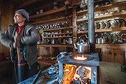 Nepal, Annapurna Region, interior of a local kitchen in Meta village. A local woman is using a butter churn. This is the Phu River valley.