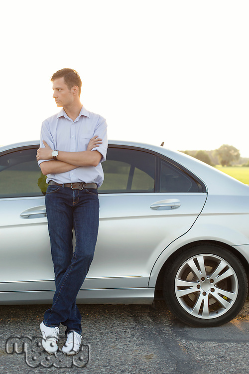 Full length of young man looking away while standing by car at countryside