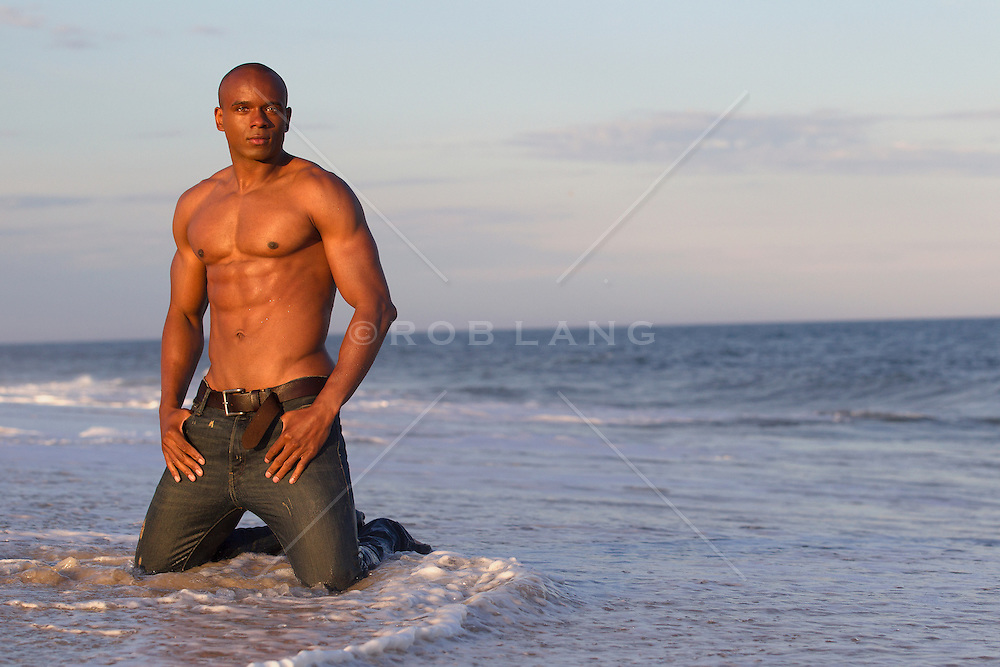 African American man with a great body on his knees wearing jeans and no shirt