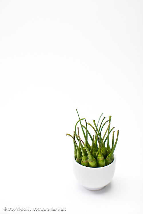 Green birds eye chillies in a white jar against a white background