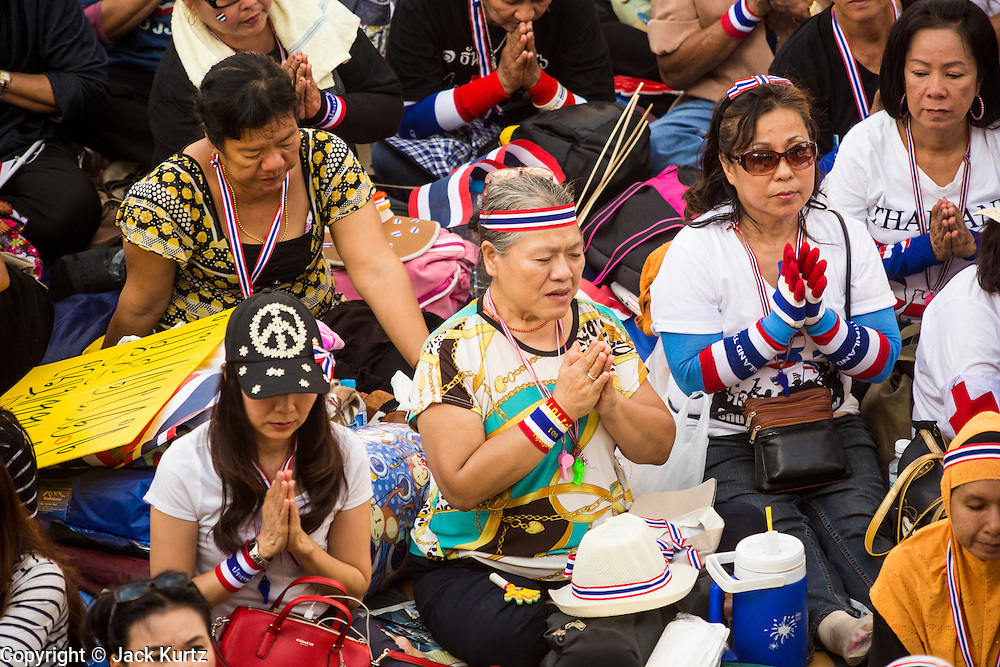 "13 JANUARY 2014 - BANGKOK, THAILAND: Anti-government protestors pray in the Asok intersection in Bangkok. Tens of thousands of Thai anti-government protestors took to the streets of Bangkok Monday to shut down the Thai capitol. The protest was called ""Shutdown Bangkok"" and is expected to last at least a week. The Shutdown Bangkok protest is a continuation of protests that started in early November. There have been shootings almost every night at different protests sites around Bangkok, including two Sunday night, but the protests Monday were peaceful. The malls in Bangkok stayed open Monday but many other businesses closed for the day and mass transit was swamped with both protestors and people who had to use mass transit because the roads were blocked.    PHOTO BY JACK KURTZ"
