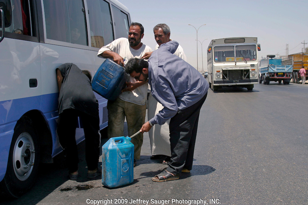 Drivers fill their vehicles with black market gas rather than wait for hours in 100-plus car lines for cheaper prices on the main highway between Baghdad and Nasiriya, in Dewanei, Iraq, on July 27, 2003. The black market gas costs 4000 Iraqi Dinar for 15 liters compared to 2750 Iraqi Dinar for 15 liters at the gas stations. Depending on the exchange rate, $5 USD equals about 7500 Iraqi Dinar.