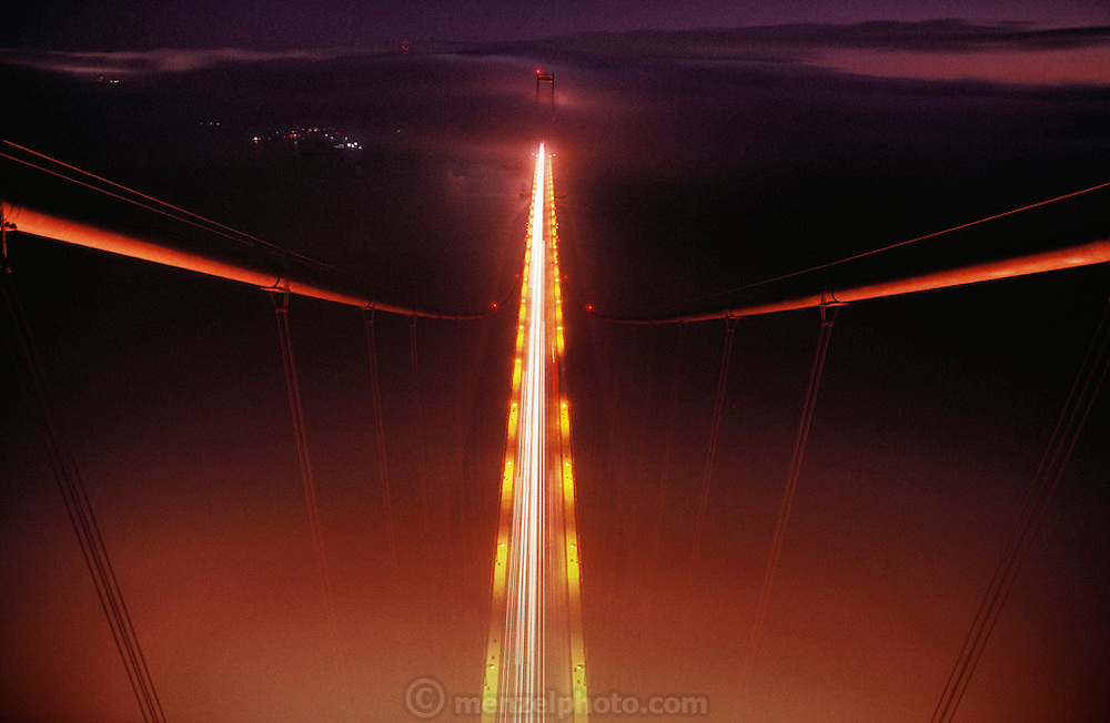 Golden Gate Bridge, San Francisco, California. View looking south from the top of the north tower.  Time exposure of early evening commuter traffic crossing the deck of the bridge.