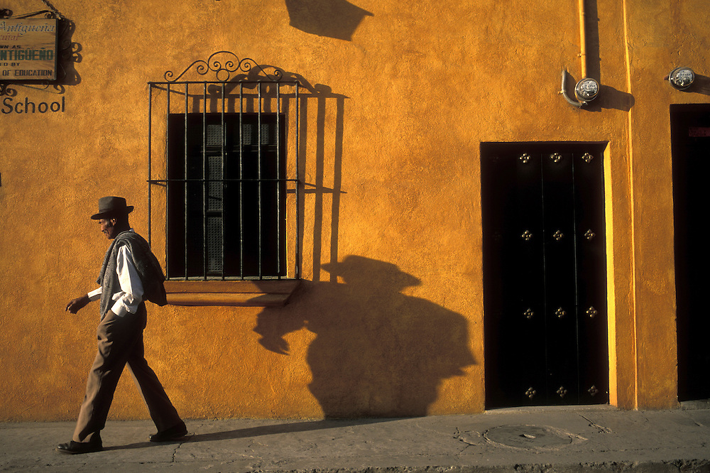 Guatemala, Antigua, Elderly man casts shadow on brightly painted wall while following religious procession