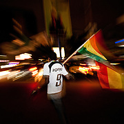 A man carries a Ghanaian flag on Oxford Street in Accra, Ghana as Ghanaians took to the streets to celebrate their defeat of the USA on 26 June 2010 during the FIFA World Cup.