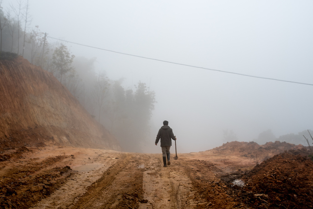 A road repair worker in Basa village, Xishuangbanna, China. The village is home to the Jinuo ethnic minority.