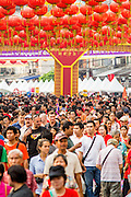 "10 FEBRUARY 2013 - BANGKOK, THAILAND:  The crowd on Yaowarat Road in Bangkok on Chinese New Year. The normally busy street, the main street in Chinatown is normally choked with traffic but it's closed to cars on Chinese New Year. Bangkok has a large Chinese emigrant population, most of whom settled in Thailand in the 18th and 19th centuries. Chinese, or Lunar, New Year is celebrated with fireworks and parades in Chinese communities throughout Thailand. The coming year will be the ""Year of the Snake"" in the Chinese zodiac.   PHOTO BY JACK KURTZ"