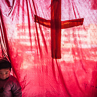 Christians eager to spread the word of God have found creative ways deliver their message in China where proselytizing is illegal. Here a child stands backstage – or to be exact, behind the stage curtain in an unused store front – before a religious play to be performed on a busy street in a small city.