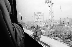 An Israeli soldier stops a Palestinian bus to check travelers' documents in the occupied West Bank.